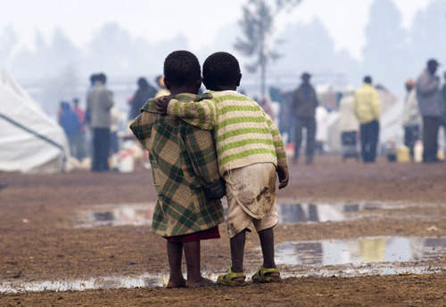 Two children stand together during heavy rainfall in a displaced persons camp in Kenya's Rift Valley