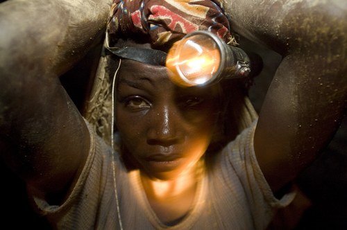 A young girl carries over 30 kgs of rocks